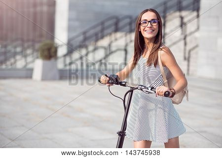 Overwhelmed with emotions. Positive beautiful woman smiling and expressing joy while riding a kick scooter