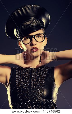 Sexual young woman alluring in fitting leather dress and a cap of police officer. Beauty, fashion.