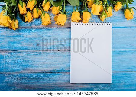 Yellow roses and paper on blue wooden table