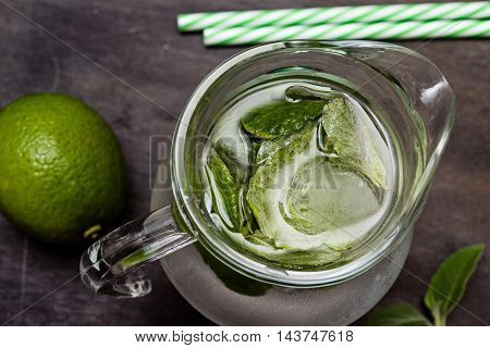 Summer drink mojito drink with ice mint and lime on dark wooden table
