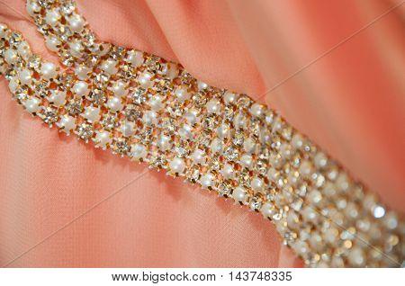 Shiny silver decoration on peach wedding dress