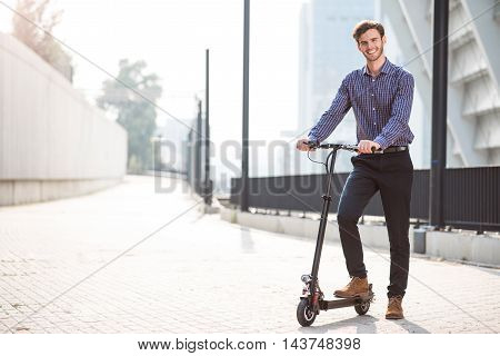 Discover new roots. Cheerful handsome man smiling and holding kick scooter while going to ride it