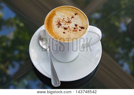 A cup of coffee in a white cup on glass background