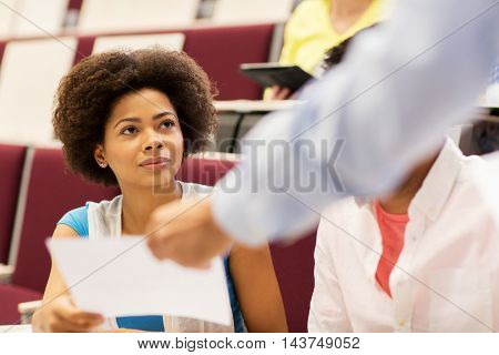 education, high school, university, learning and people concept - teacher giving test to student girl on lecture