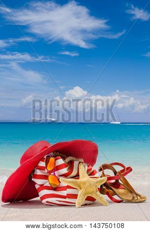 Summer beach bag with straw hat, sunglasses and starfish on sandy beach