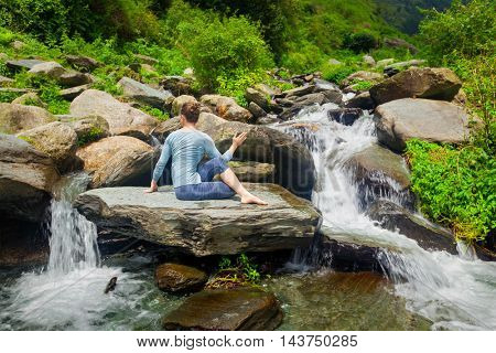 Yoga exercise outdoors -  woman doing Ardha matsyendrasanaasana asana - half spinal twist pose at tropical waterfall in Himalayas in India