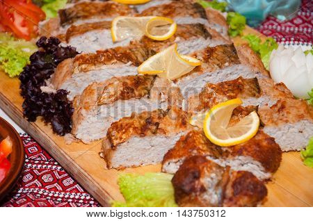 Meat pie on a wooden board decorated with lemon and herbs