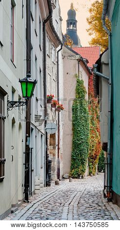 Narrow street in old Riga city, Latvia. Walking through medieval streets of old Riga tourists can feel unforgettable atmosphere of the Middle Ages and unique Gothic architecture