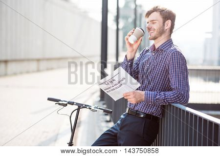 Active start of the day. Delighted positive man smiling and drinking coffee while standing near kick scooter