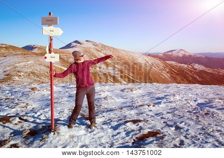 Smiling Female Hiker staying at Path Sign and admiring scenic View in Winter Mountains pointing with her Hand to Horizon