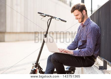 Rise your mood. Cheerful handsome man using laptop and sitting near kick scooter while expressing gladness