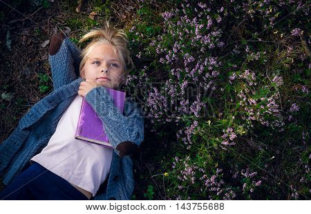 Beautiful blonde girl reading a book in the forest. Education.