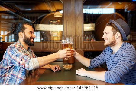 people, leisure, friendship and party concept - happy male friends drinking draft beer at bar or pub and clinking glasses