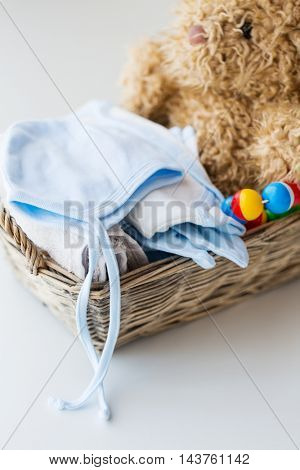 babyhood, motherhood, clothing and object concept - close up of baby clothes and toys for newborn boy in basket