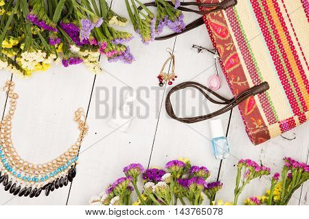 Straw Bag, Colorful Flowers, Cosmetics Makeup, Bijou And Essentials On White Wooden Background
