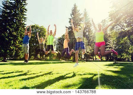fitness, sport, friendship and healthy lifestyle concept - group of happy teenage friends jumping high outdoors