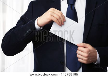 Businessman putting envelope with money in suit pocket closeup
