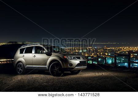 Saratov, Russia - November 27, 2014: Car Mitsubishi Outlander stand on road near city panorama at night