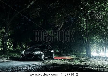 Saratov, Russia - June 12, 2015: Black car BMW E90 stand on road in darkness forest at night