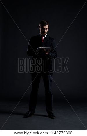 Businessman with a tablet computer over black background. Business, office, technology and internet concept.