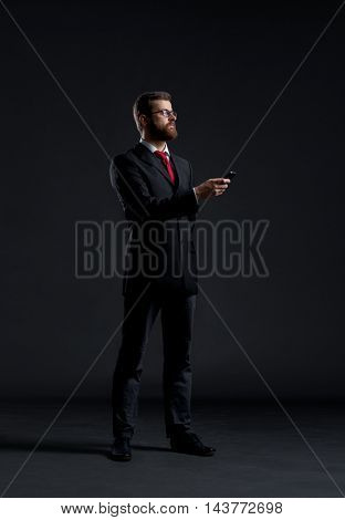 Businessman sending message with a smartphone over black background. Business, office and internet communication concept.