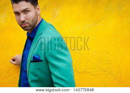 Fashionable brunette guy posing on background of yellow wall