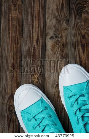 blue sneakers on wooden surface