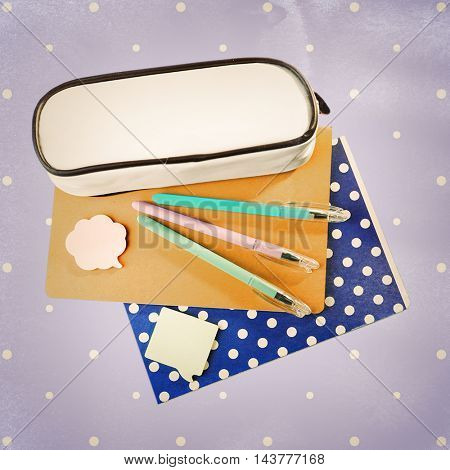 Colorful pens, pencil box and copybooks on color background. School concept.