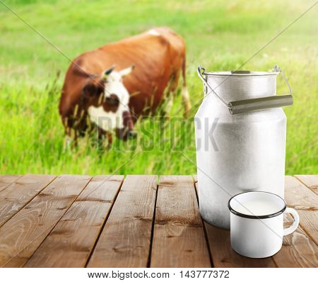 Retro can and cup of milk on wooden table. Cow on pasture, blurred background.