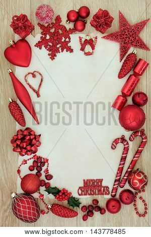 Red christmas background border decorations and tree baubles over light oak background.