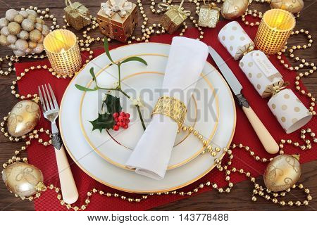Christmas dinner table setting with white plates, antique knife and fork, linen serviette, holly, mistletoe, gold bauble decorations, candles, and cracker on red place mat over oak background.