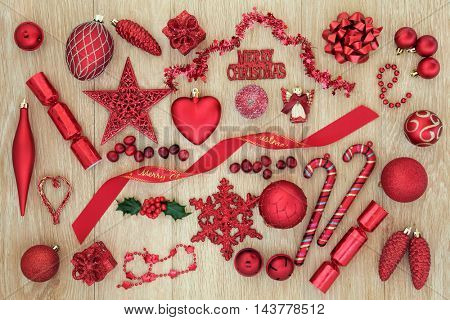 Red christmas decorations and tree baubles over light oak background.