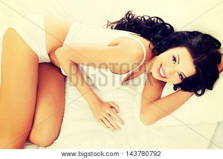 Happy sensual woman lying in bed