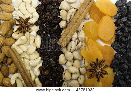 Dried fruits and nuts with spices arranged in rows as a background