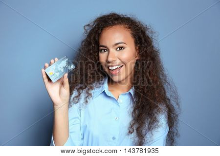 Attractive woman holding credit card on blue background
