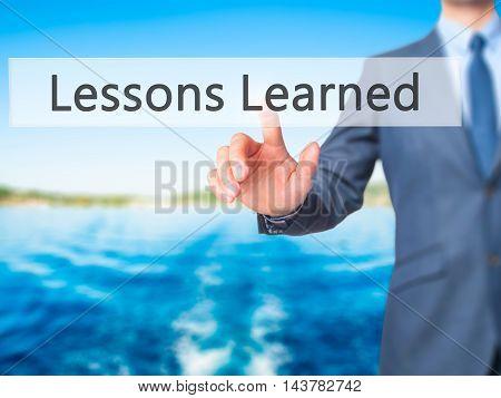 Lessons Learned -  Businessman Press On Digital Screen.