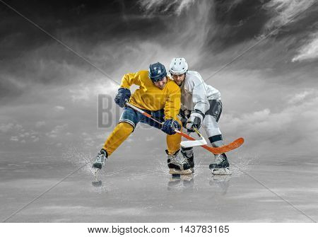 Ice hockey players in action outdoor under sky.