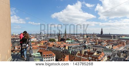 Copenhagen, Denmark - August 15, 2016: People enjoying panoramic view over the city from the bell tower of Vor Frue Cathedral