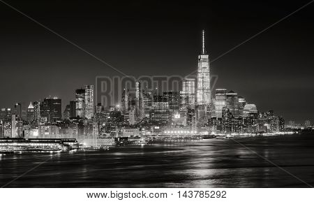 Skyscrapers of New York City Financial District illuminated at night. Aerial panoramic view of Lower Manhattan and the Hudson River in Black & White