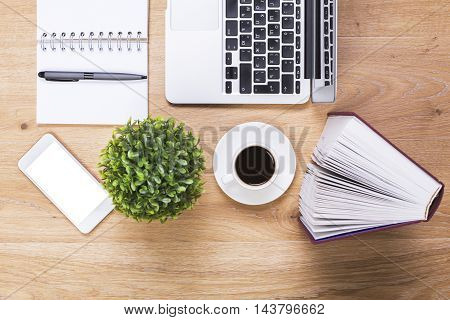 Closeup of wooden office desktop with blank white phone plant coffee cup hardcover book spiral notepad with pen and laptop. Mock up