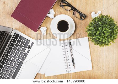 Top view of wooden office desktop with open spiral notepad pen plant coffee cup glasses closed book laptop keyboard and crumpled paper balls
