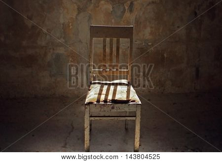 Abandoned chair in the middle of a dark rood