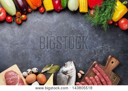 Vegetables, fish, meat and ingredients cooking. Tomatoes, eggplants, corn, beef, eggs, cheese. Top view with copy space on stone table