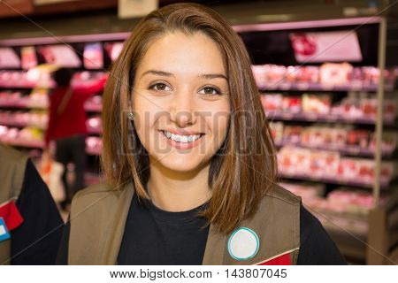 Sales assistant in supermarket demonstrating dairy products food