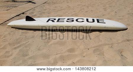 White Coast Guard Rescue Surfboard On The Sea Beach