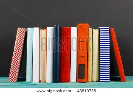 Composition with old vintage colorful hardback books, diary on wooden deck table and black board background. Books stacking. Back to school. Copy Space. Education background