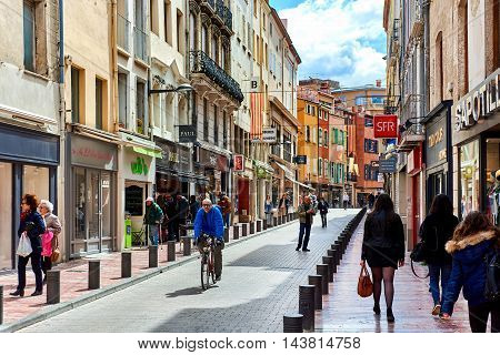 Perpignan France - April 8, 2016: People walking in the Perpignan main commercial street in the old town. It is one of the most famous shopping street in the city a narrow but long street with plenty of stores. Pyrenees-Orientales France
