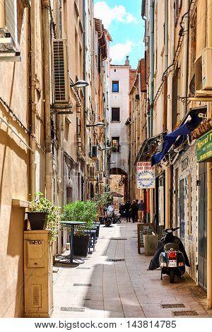 Perpignan France - April 8 2016: Charming narrow street in old town of Perpignan in springtime. Pyrenees-Orientales France