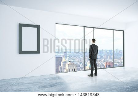 Businessman looking out of window in concrete interior with blank picture frame and city view. Mock up 3D Rendering