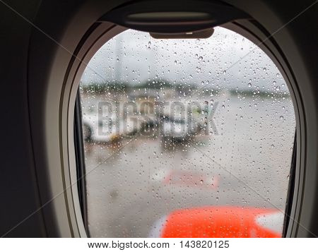 Water drop on mirror window of airplane in rainy day while landing at airport. Safety in transportation and travel concept.
